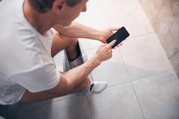 Vista superior de um homem adulto de cabelos curtos em uma camiseta de algodão usando seu telefone celular