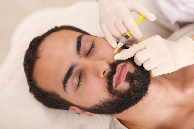 Vista superior de um homem barbudo recebendo preenchimento facial injetado por cosmetologista