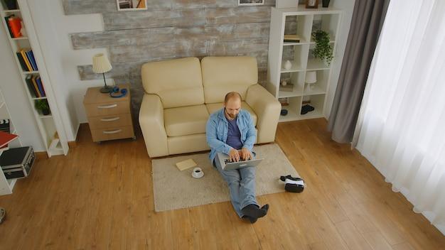 Vista superior de um homem caucasiano trabalhando em casa em um laptop e tomando café enquanto está sentado no chão