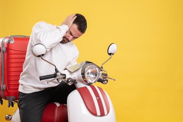 Vista superior de um homem com problemas sentado em uma motocicleta com uma mala segurando um mapa com dor de cabeça em fundo amarelo isolado