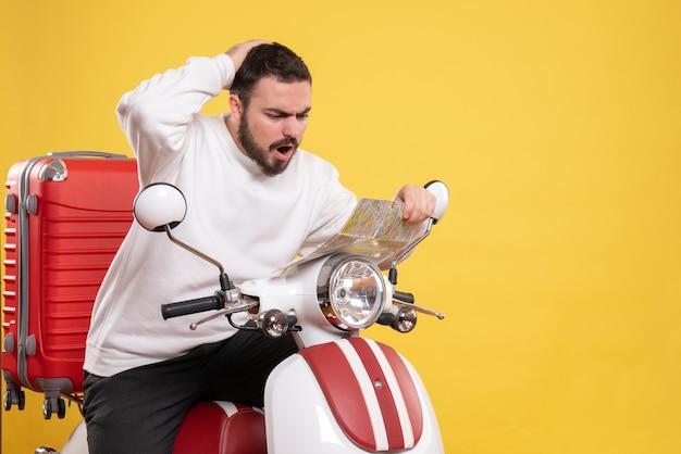 Vista superior de um homem curioso sentado em uma motocicleta com uma mala segurando um mapa em fundo amarelo isolado