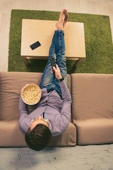 Vista superior de um homem descalço assistindo tv com pipoca