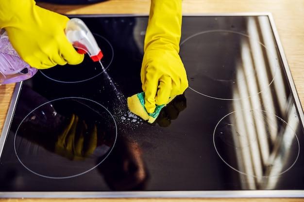 Vista superior de um homem digno pulverizando produto de limpeza no fogão e esfregando com uma esponja. nas mãos estão as luvas de borracha.