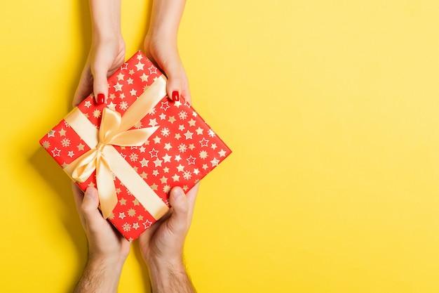 Vista superior de um homem e uma mulher dando e recebendo presentes para umas férias em fundo colorido