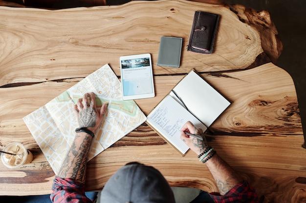 Vista superior de um homem irreconhecível com tatuagens sentado à mesa de madeira e fazendo anotações enquanto pensa no tempo de viagem