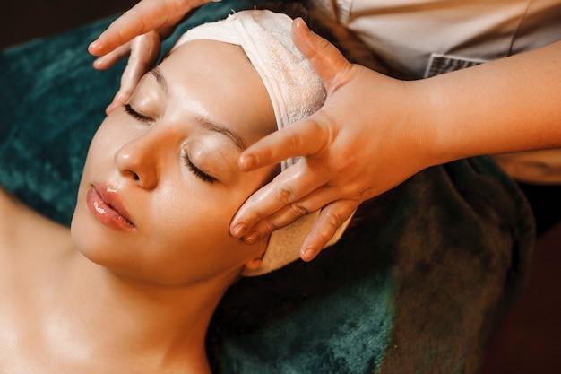 Vista superior de um incrível rosto de mulher branca, encostado em uma cama de spa com os olhos fechados, fazendo uma massagem anti-idade por um cosmetologista em um centro de spa.