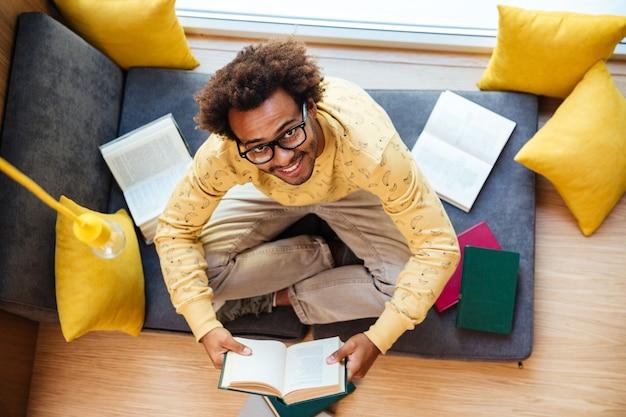 Vista superior de um jovem africano alegre de óculos sentado e lendo em casa