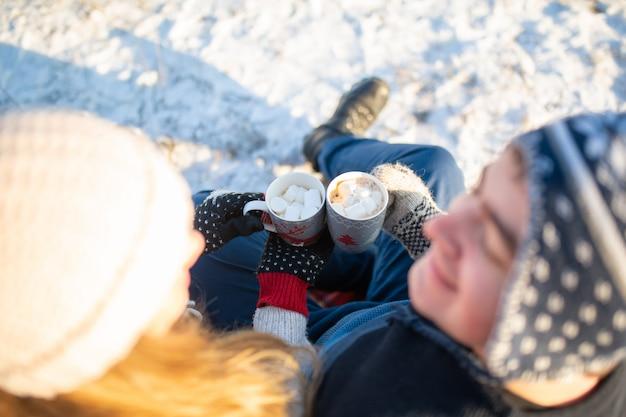 Vista superior de um jovem casal apaixonado bebe um chocolate quente com marshmallows