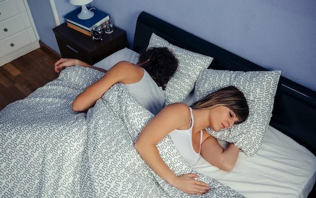 Vista superior de um jovem casal dormindo de costas na cama