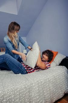 Vista superior de um jovem casal em confinamento por um vírus fazendo uma luta de travesseiros na cama