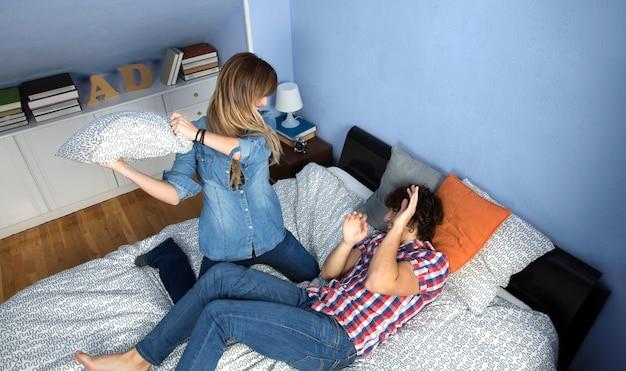 Vista superior de um jovem casal fazendo uma luta de travesseiros na cama