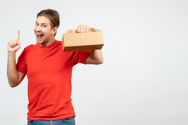 Vista superior de um jovem confiante e feliz em uma blusa vermelha segurando uma caixa e apontando para cima em um fundo branco