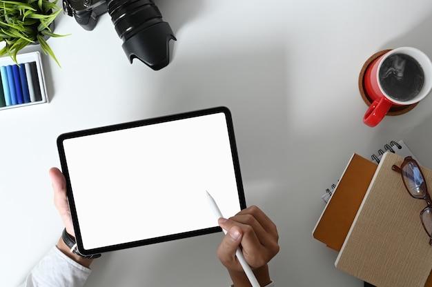 Vista superior de um jovem designer profissional desenhando seu projeto com um tablet em uma área de trabalho confortável