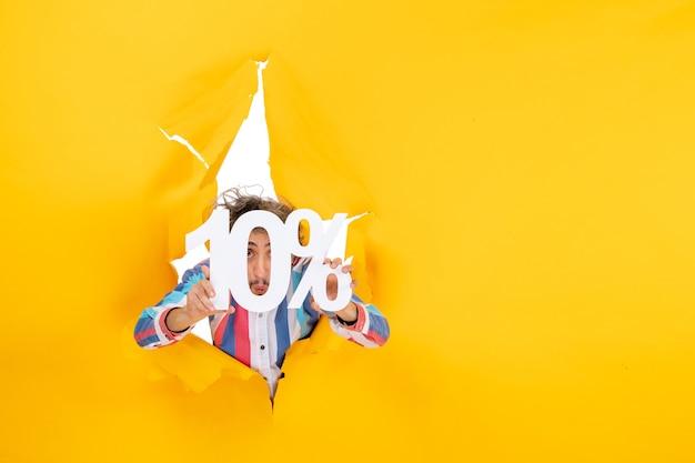 Vista superior de um jovem mostrando dez por cento na frente de seu rosto em um buraco rasgado em papel amarelo
