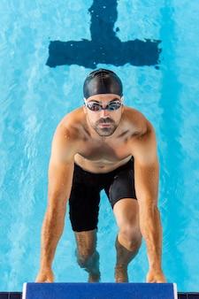 Vista superior de um jovem nadador masculino em uma piscina olímpica