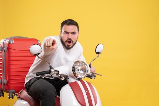 Vista superior de um jovem nervoso sentado em uma motocicleta com uma mala e apontando para a frente em um fundo amarelo isolado
