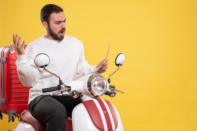 Vista superior de um jovem nervoso sentado em uma motocicleta com uma mala segurando um mapa em fundo amarelo isolado