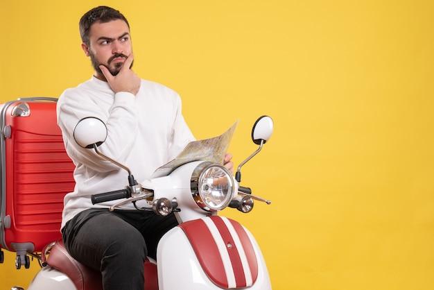 Vista superior de um jovem sentado em uma motocicleta com uma mala e se sentindo confuso sobre um fundo amarelo isolado