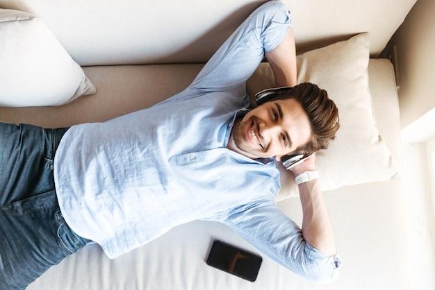 Vista superior de um jovem sorridente, deitado no sofá