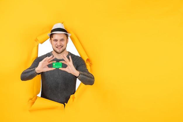 Vista superior de um jovem sorridente segurando o cartão do banco em uma parede amarela rasgada