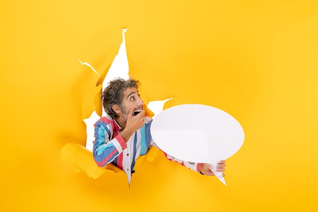 Vista superior de um jovem surpreso apontando para uma página em branco com espaço livre em um buraco rasgado em papel amarelo
