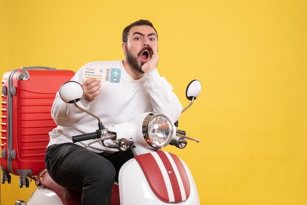 Vista superior de um jovem viajante sentado em uma motocicleta com uma mala segurando um bilhete chamando alguém em amarelo