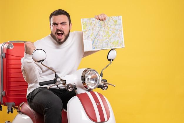 Vista superior de um jovem zangado sentado em uma motocicleta com uma mala segurando um mapa em fundo amarelo isolado
