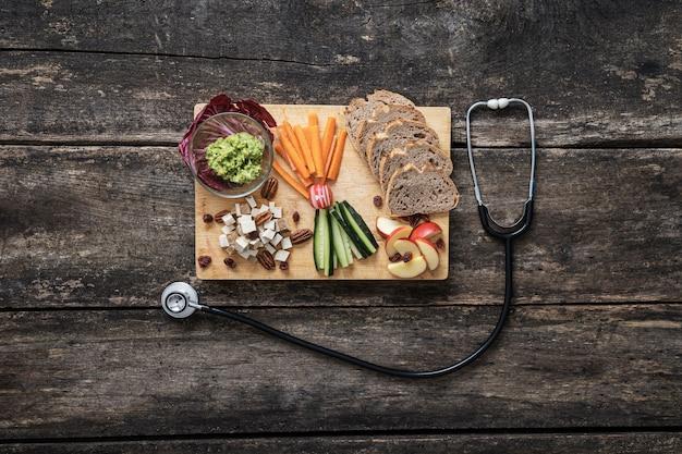 Vista superior de um lanche vegano delicioso e saudável de pão de massa fermentada, vegetais crus, cubos de tofu e pasta de abacate servidos em uma placa de madeira