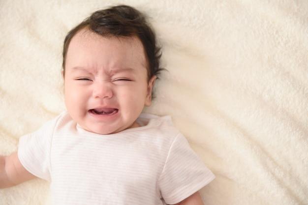 Vista superior de um lindo bebê asiático chorando