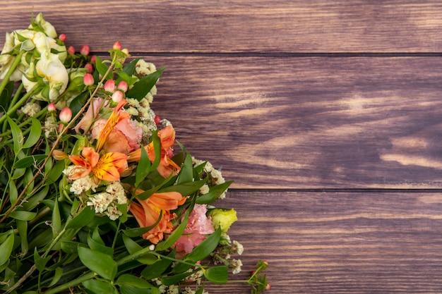 Vista superior de um lindo buquê de flores coloridas com folhas em madeira