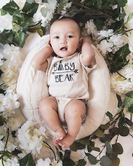 Vista superior de um lindo menino em uma cesta cercada por flores