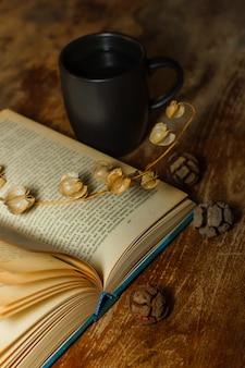 Vista superior de um livro antigo com caneca de café e flores secas na mesa de madeira. vertical