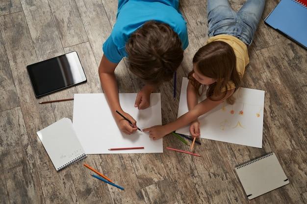 Vista superior de um menino caucasiano e uma menina deitada no chão de madeira em casa e desenhando em um branco