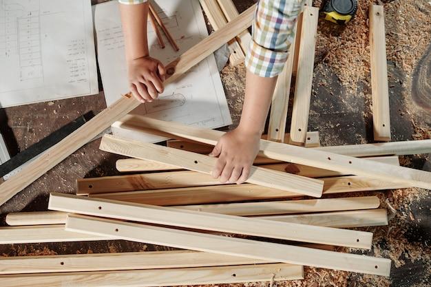 Vista superior de um menino irreconhecível usando esboços ao montar móveis em uma oficina de carpintaria