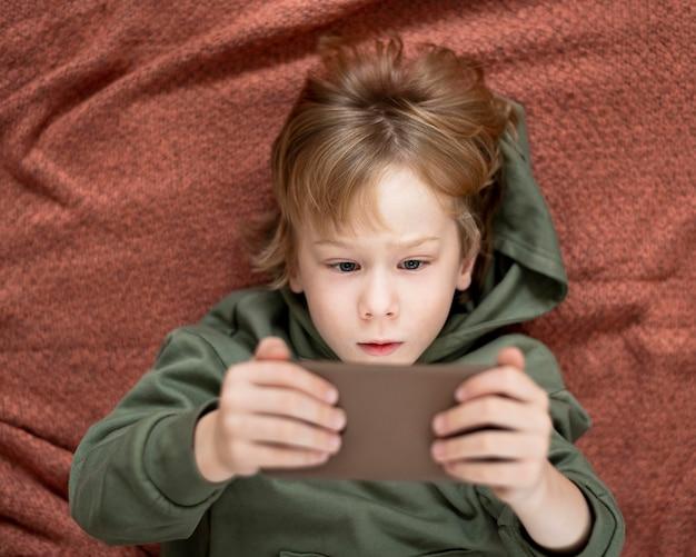 Vista superior de um menino usando smartphone na cama