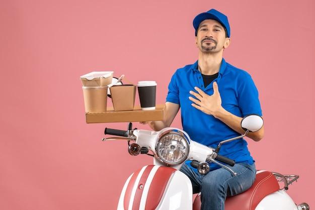 Vista superior de um mensageiro confiante sorridente usando um chapéu sentado na scooter em um pêssego pastel