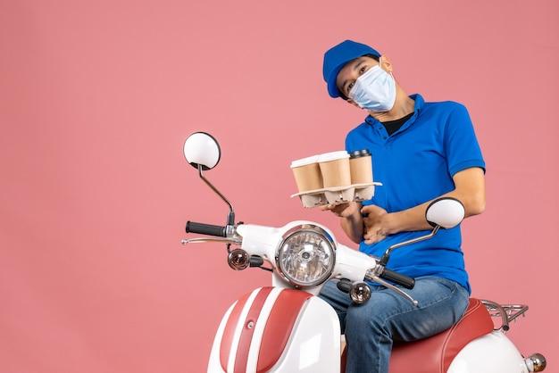 Vista superior de um mensageiro incerto, mascarado, usando um chapéu, sentado na scooter, mostrando pedidos em pêssego pastel