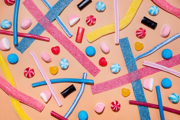 Vista superior de um misto de doces doces coloridos e pirulitos