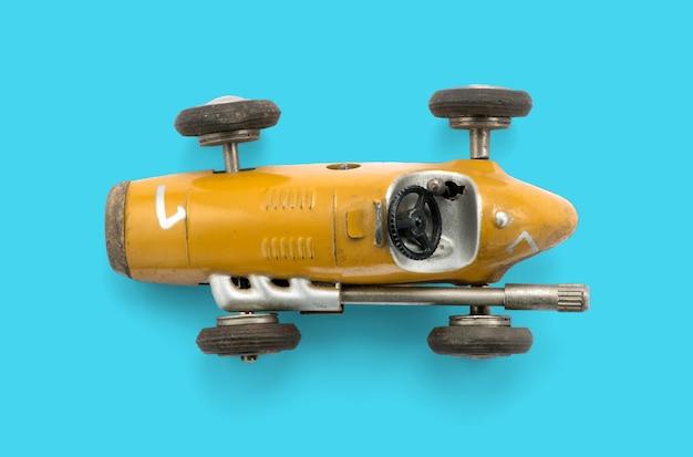 Vista superior de um modelo surrado de um veículo de corrida vintage isolado em um fundo ciano