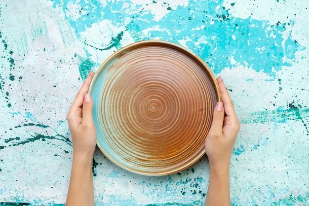 Vista superior de um molde redondo marrom seguro por uma fêmea em uma refeição de bolo azul claro