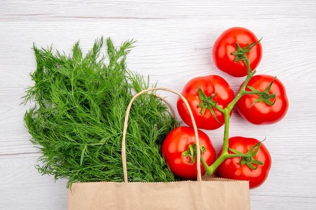 Vista superior de um molho de cebola verde em uma cesta e tomates com haste no fundo branco