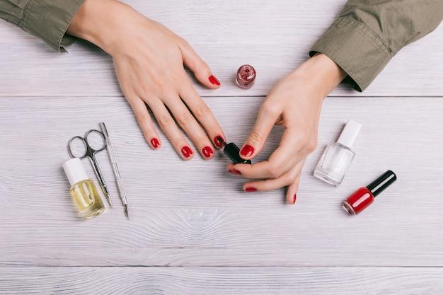 Vista superior, de, um, mulher, fazendo, um, manicure, e, pintar pregos, com, vermelho, laca