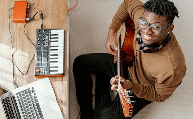 Vista superior de um músico sorridente em casa tocando guitarra e mixando com o laptop