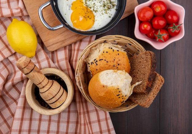 Vista superior de um ovo frito em uma frigideira com um balde de pães, tomate e limão em uma toalha xadrez