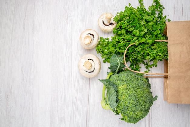 Vista superior de um pacote de brócolis de cogumelos verdes frescos em uma cesta no lado esquerdo sobre fundo branco