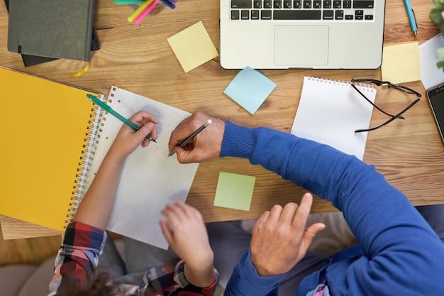 Vista superior de um pai latino carinhoso ajudando seu filho com a lição de casa, explicando a tarefa de fazer anotações