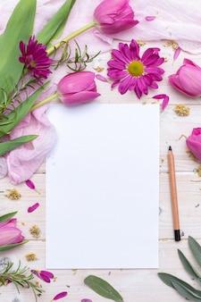 Vista superior de um papel em branco e um lápis decorado com flores roxas