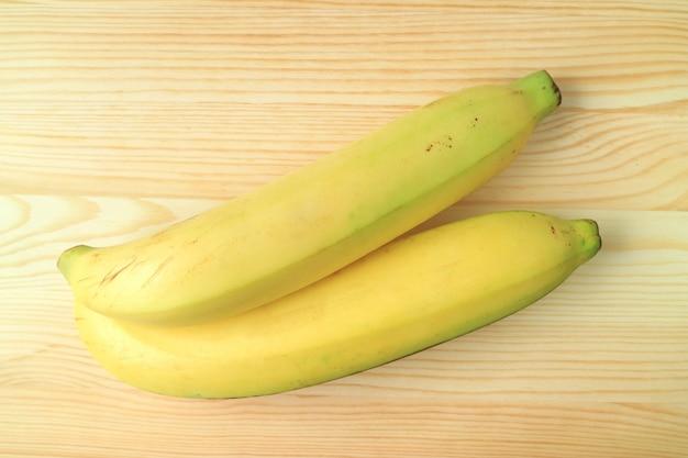 Vista superior de um par de bananas maduras amarelas brilhantes isoladas no fundo de madeira