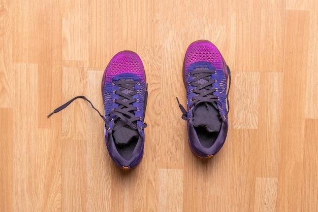 Vista superior de um par de tênis roxo de sapatos esporte no parquet de madeira no ginásio