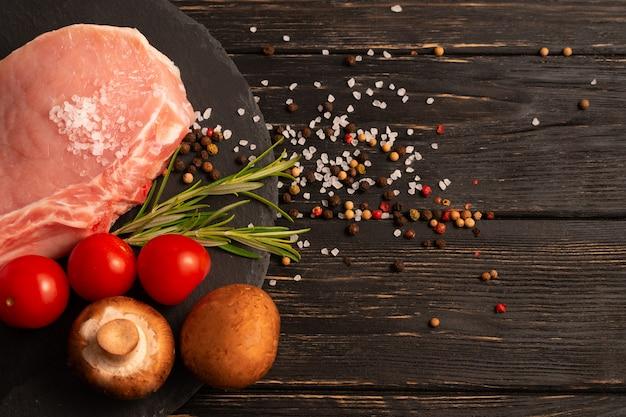 Vista superior de um pedaço de bisteca de porco crua com tomate cereja